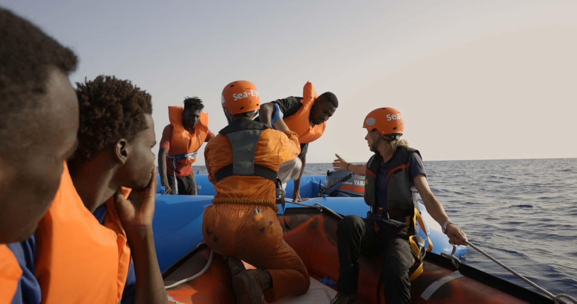 Seenotrettungseinsatz Sea Eye auf dem Mittelmeer Menschen werden an Bord genommen